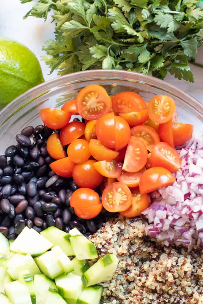 a bowl of black beans, tomatoes, onions, quinoa, and cucumbers