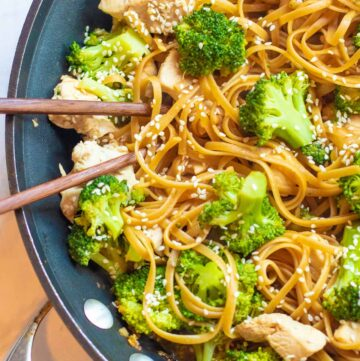 a pan with noodles, chicken, broccoli and chopsticks.