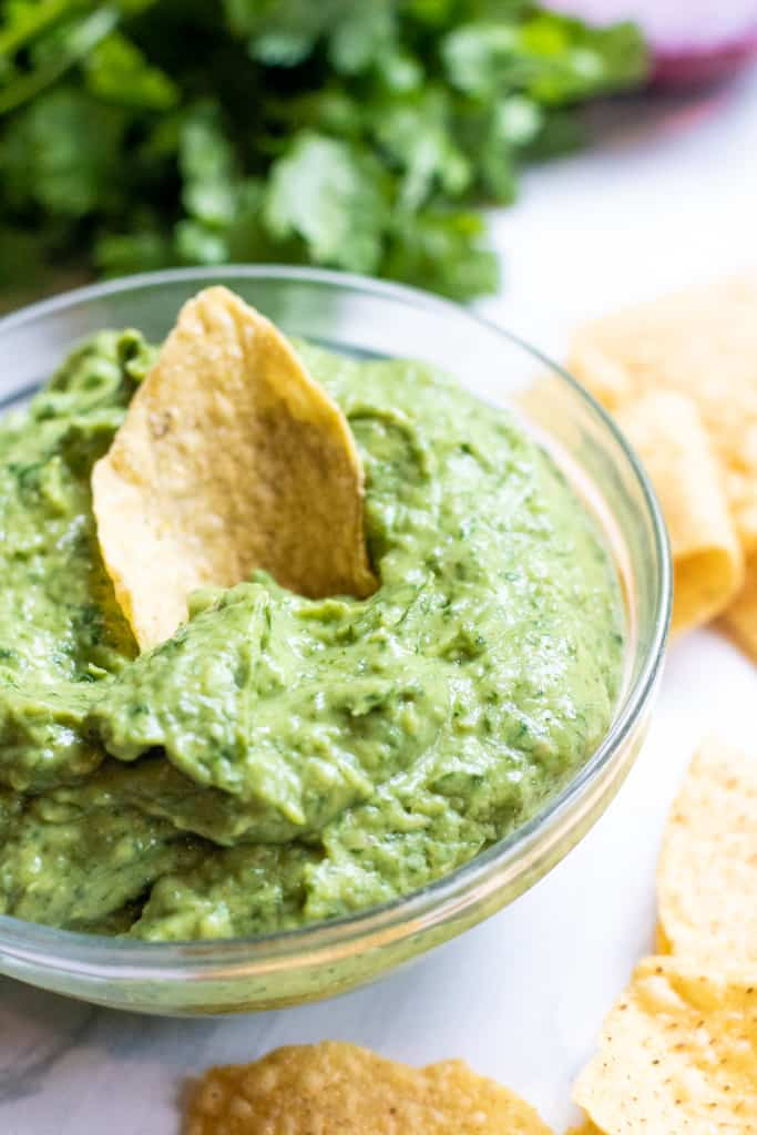 This Fresh Spinach Guacamole takes the classic dip and makes it even healthier by adding some fresh spinach while keeping the classic guacamole flavors! #guacamole #spinach #dip #recipe #appetizers #simple
