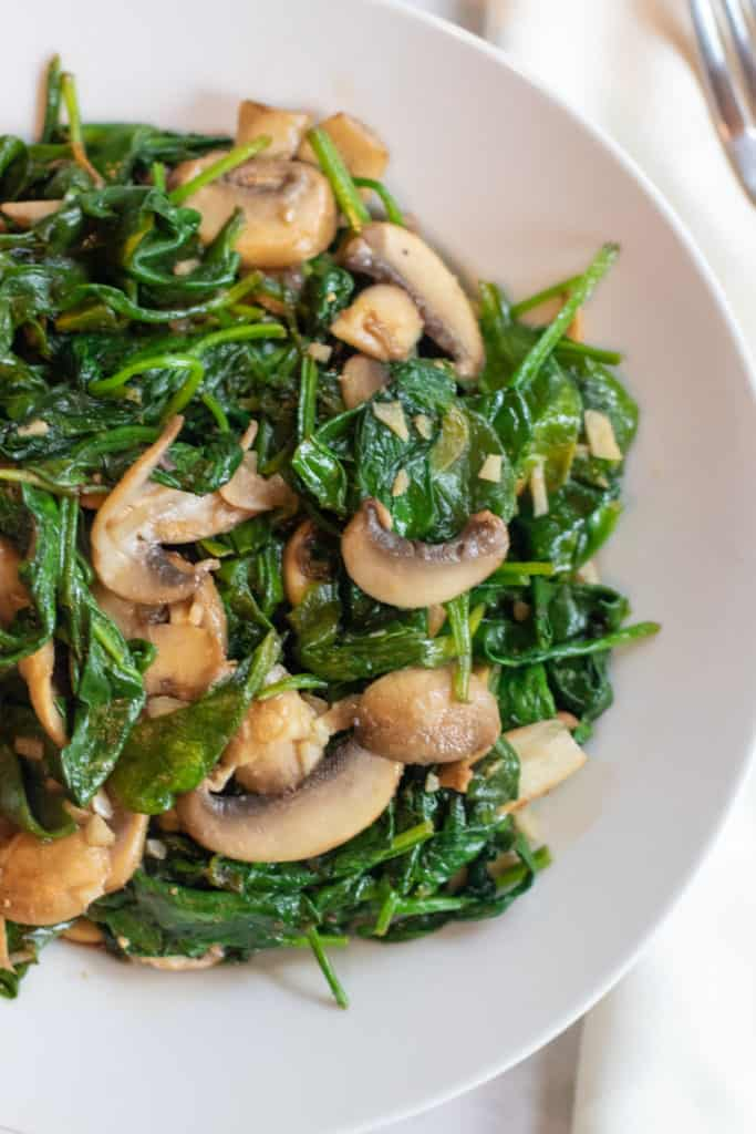 An incredibly fast and easy side dish, these Balsamic Spinach and Mushrooms are a new favorite in our house that's packed full of flavor and nutrition! #spinach #mushrooms #sauteedspinach #recipes #easy #sauteed #vegan #glutenfree #healthy