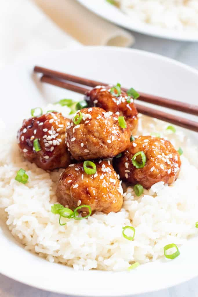 sesame seed and green onion topped meatballs on a bed of rice
