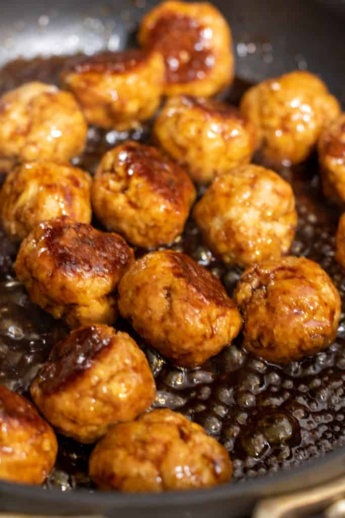 meatballs cooking in a glaze in a pan