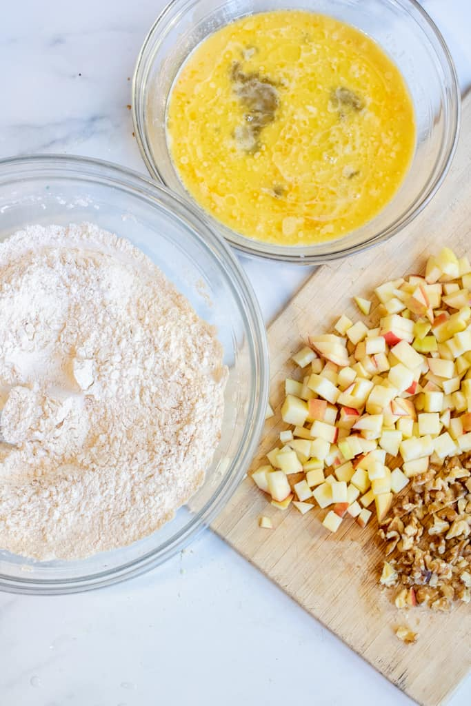 a bowl of mixed flour, eggs, and a cutting board of diced apples and walnuts.