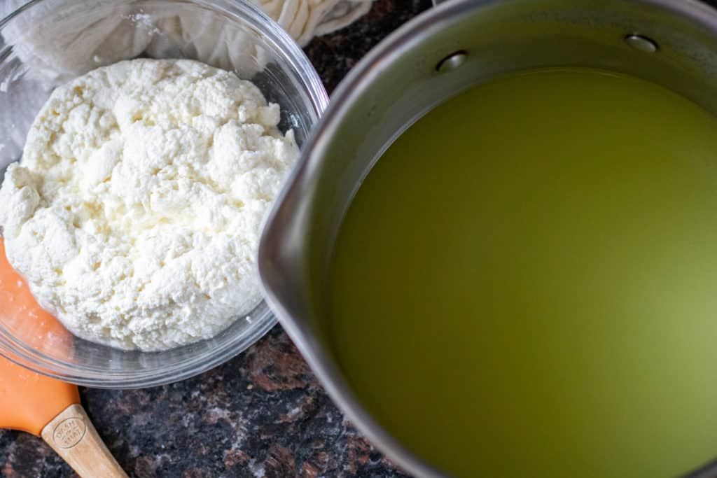 fresh ricotta cheese in a bowl next to a pot of whey