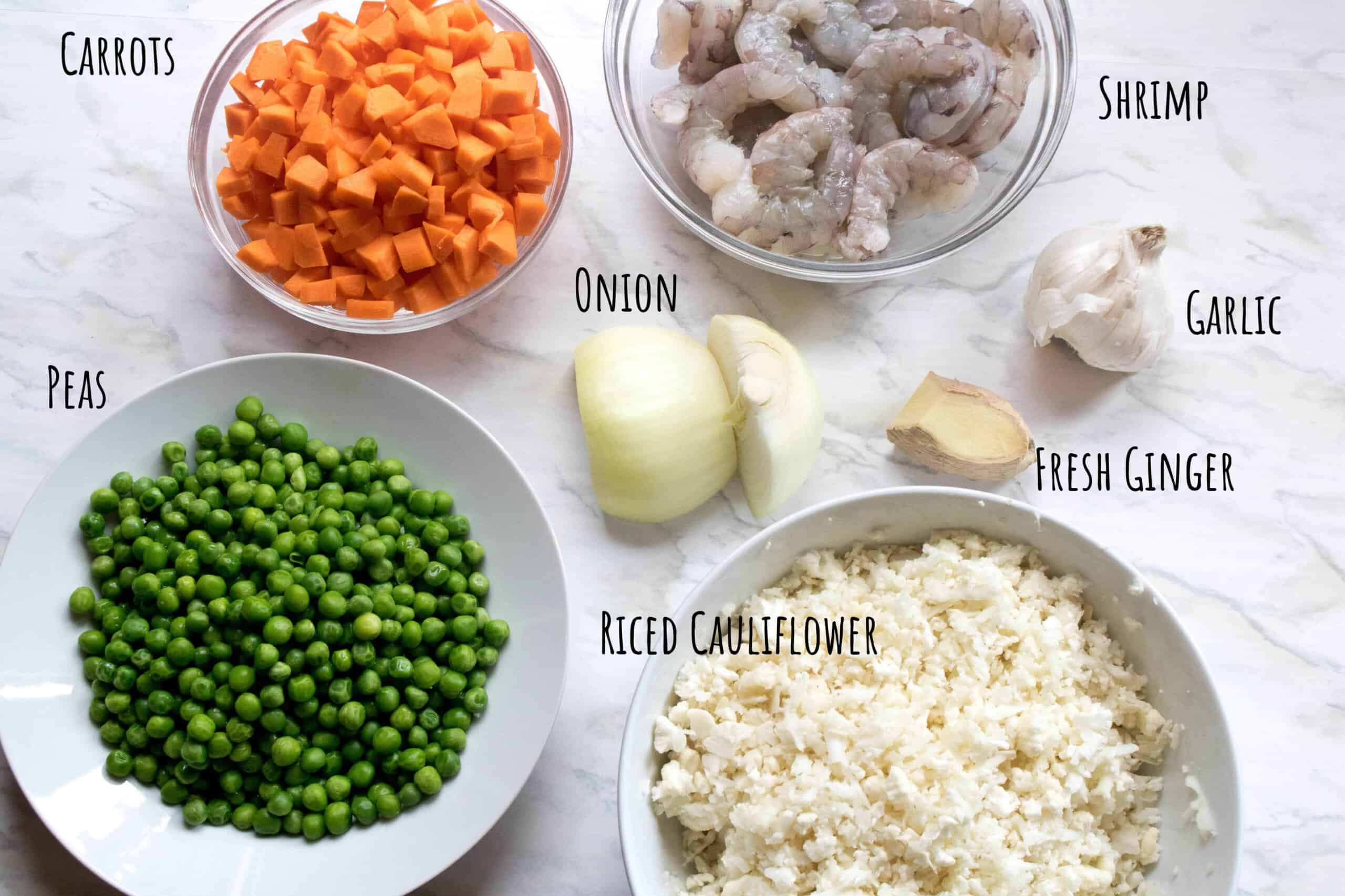 peas, carrots, onion, shrimp, garlic, and ginger and riced cauliflower on counter