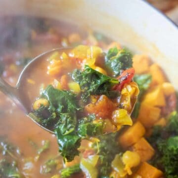 dutch oven of cooked chickpeas, sweet potato, kale soup