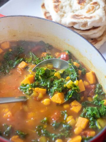 dutch oven of cooked chickpeas, sweet potato, kale soup with ladle.
