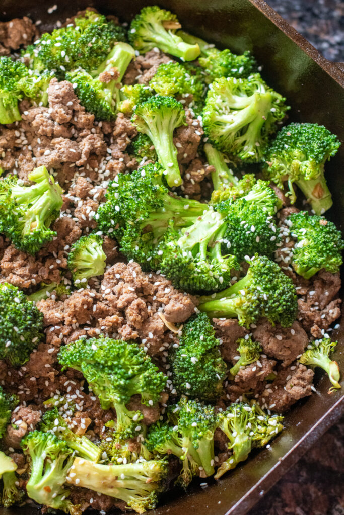 cooked ground beef and broccoli in a cast iron