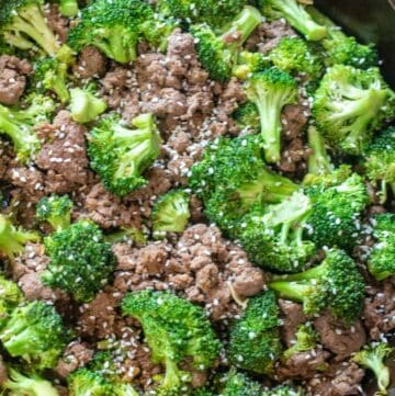 cooked ground beef and broccoli with sesame seeds in a cast iron.