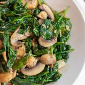 cooked spinach and mushrooms in a bowl.