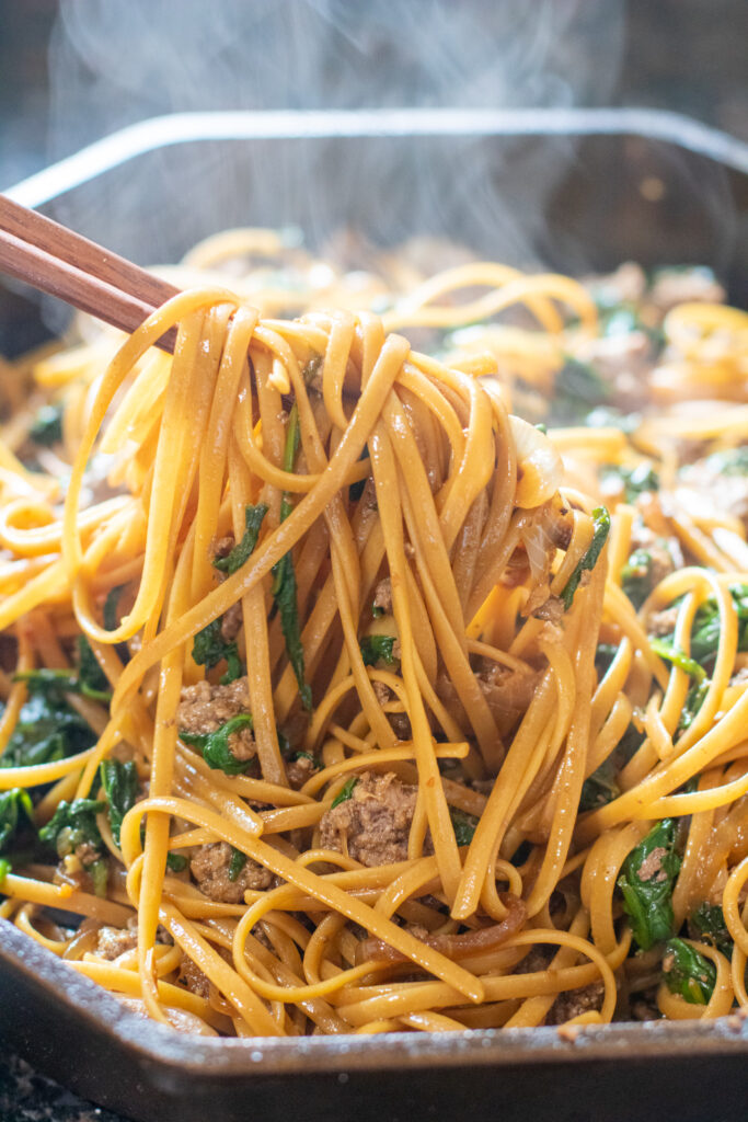 chopsticks holding up cooked noodles with beef and spinach in cast iron.