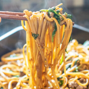 chopsticks holding cooked noodles with spinach and ground beef from cast iron