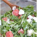 arugula watermelon feta salad in a large bowl with a wooden spoon