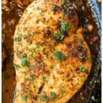 garlic butter chicken cooked in a pan topped with fresh parsley