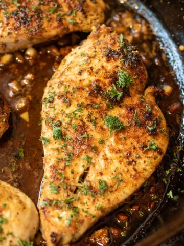 cooked garlic butter chicken in a pan with fresh parsley