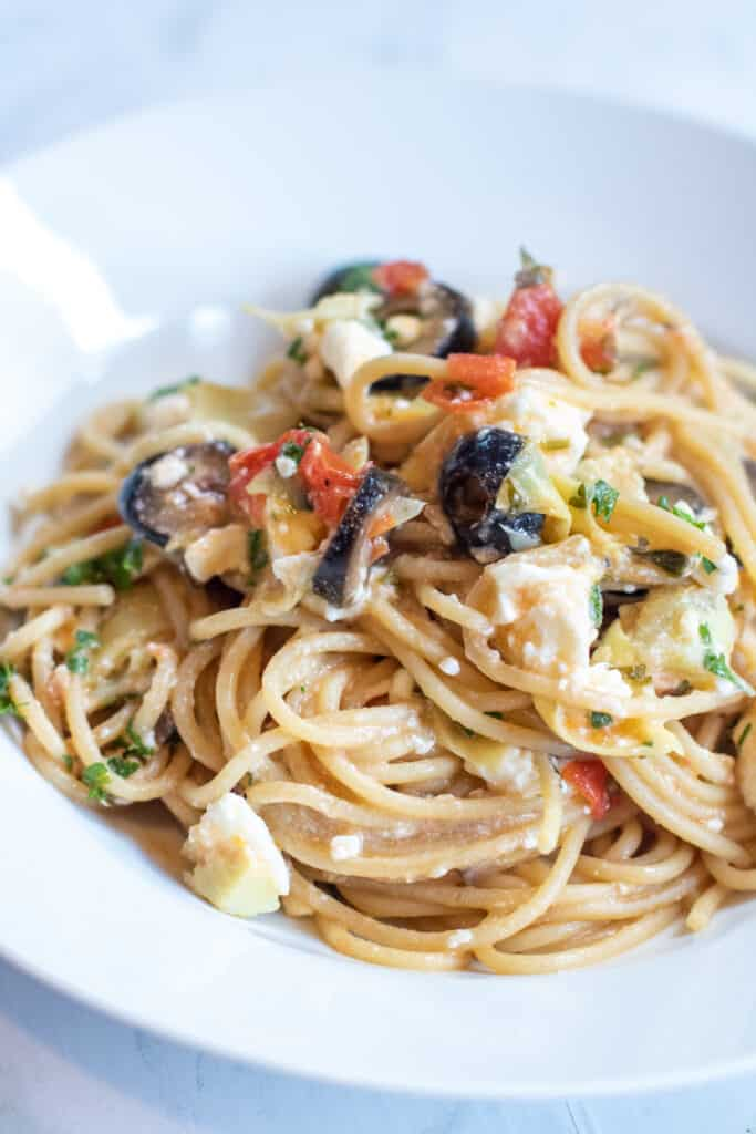 greek pasta with olives feta and tomatoes on a plate