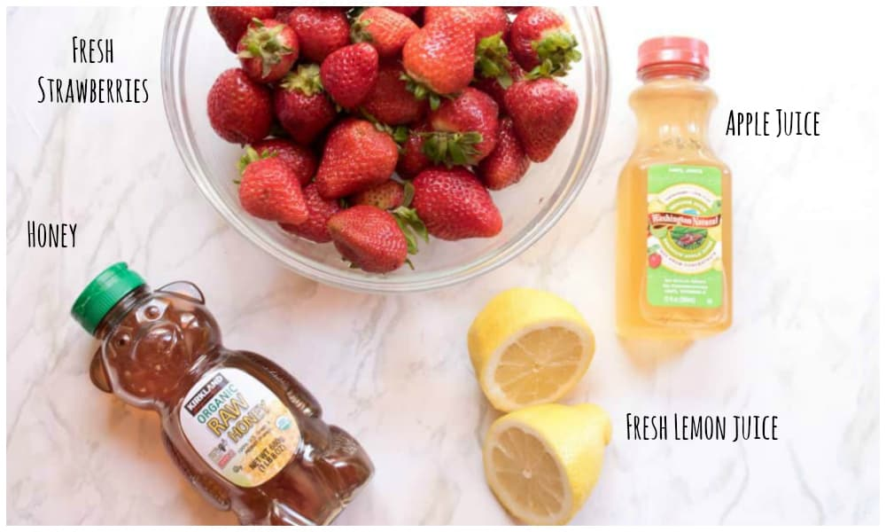 strawberries, honey, lemon, and apple juice on a counter.