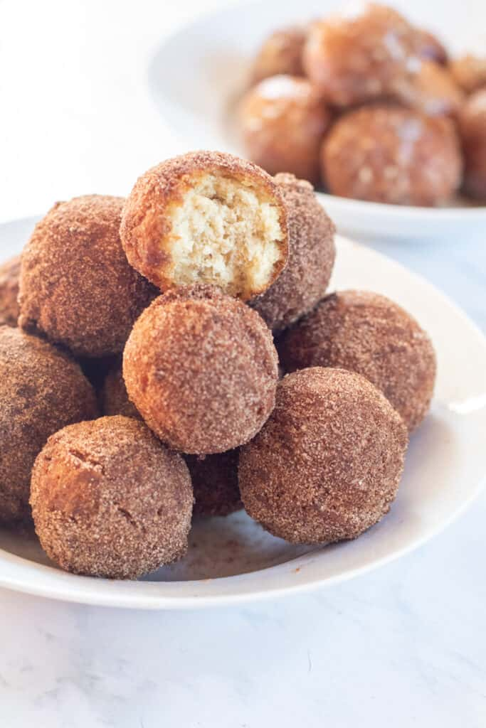 bowl of cinnamon sugar munchkins with glazed munchkins in a bowl behind