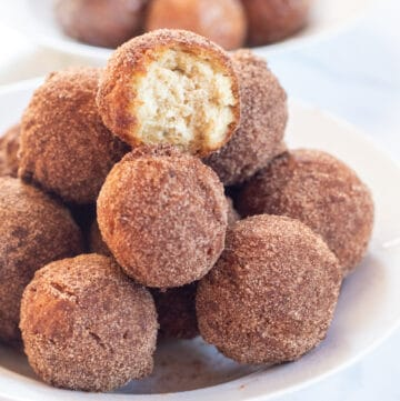 bowl of cinnamon sugar munchkins with glazed munchkins in a bowl behind.