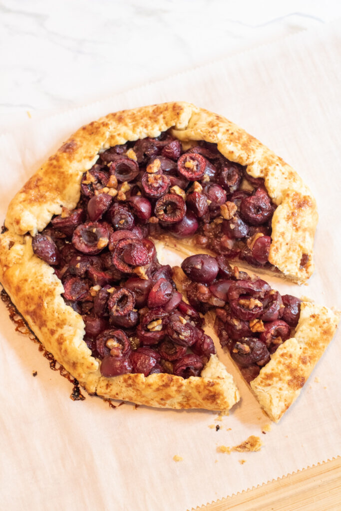 a baked rustic galette with cherries and pecans