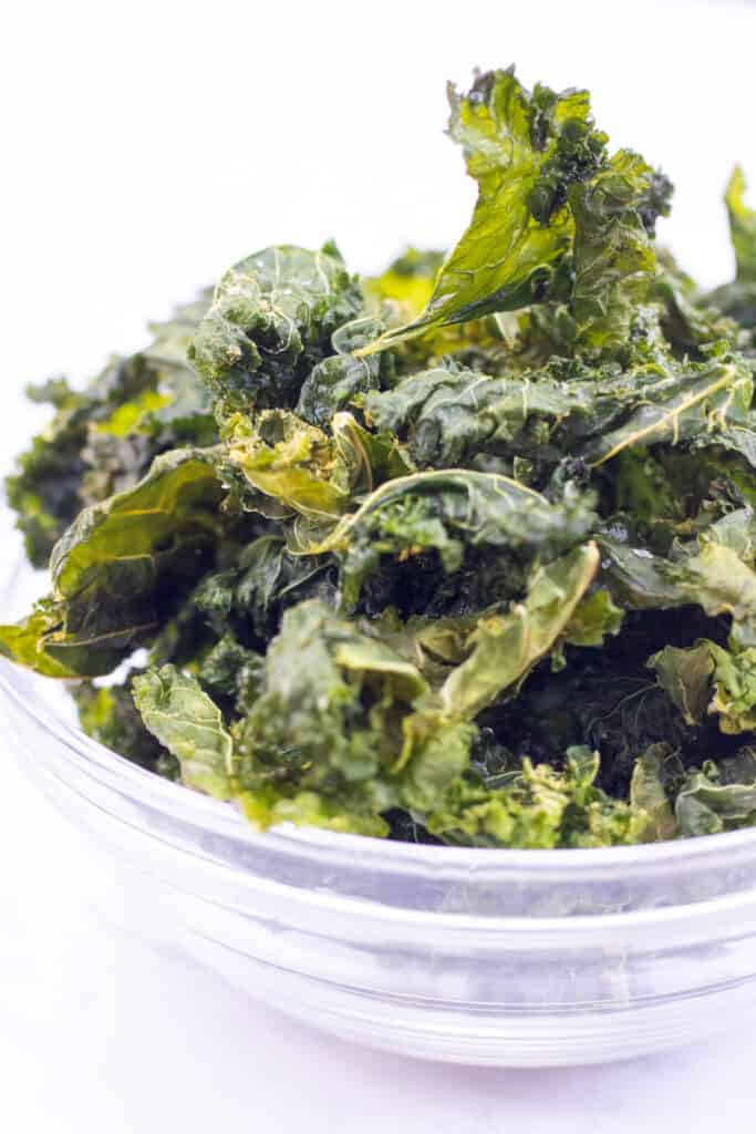 a bowl filled with crispy kale chips.