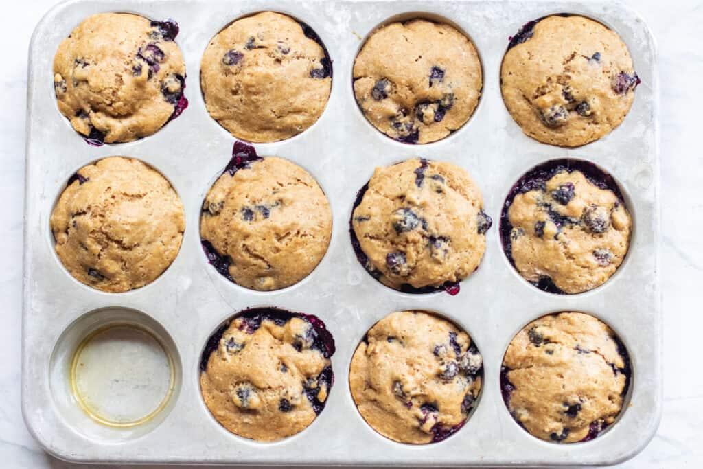 a muffin tin with baked blueberry muffins