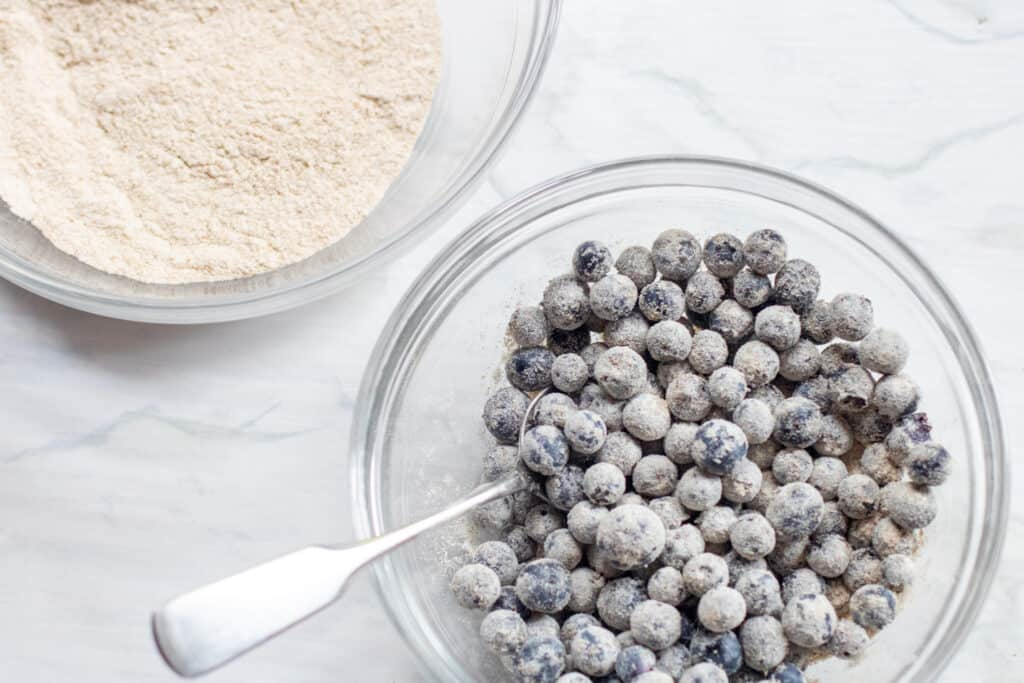 a bowl of flour and a bowl of flour coated blueberries with a spoon