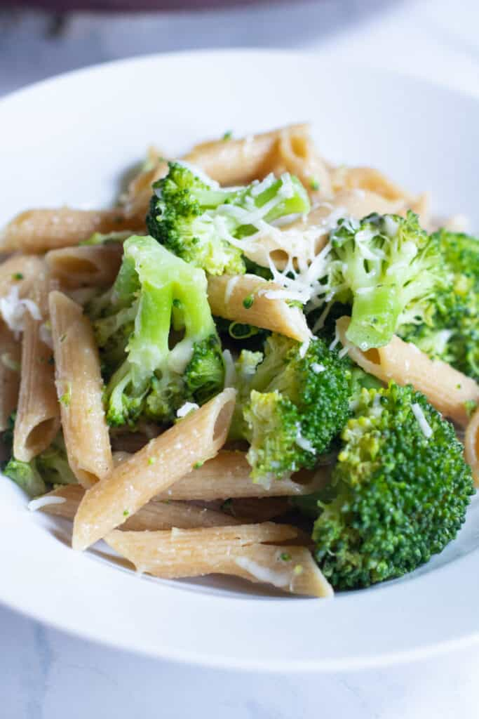 a plate of cooked penne and broccoli