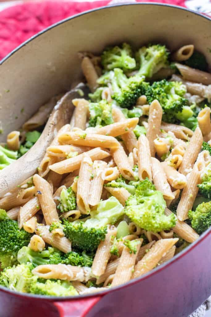 a pot of cooked penne and broccoli with a wooden spoon