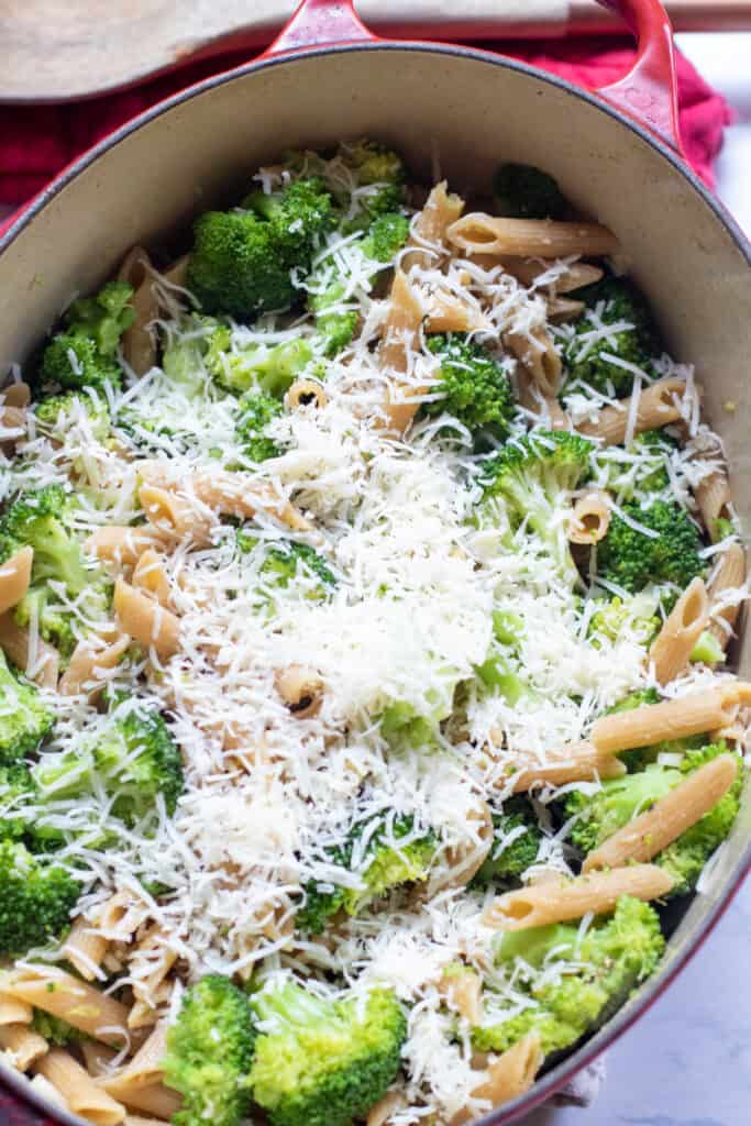 pot with cooked penne, broccoli, topped with shredded cheese