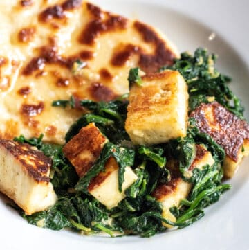 a plate with naan and paneer and spinach