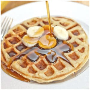a plate of a banana waffles with syrup being poured on top.