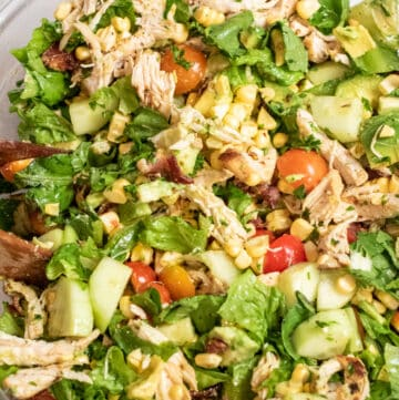 grilled chicken green salad with tomatoes, corn, and avocado in a large bowl.