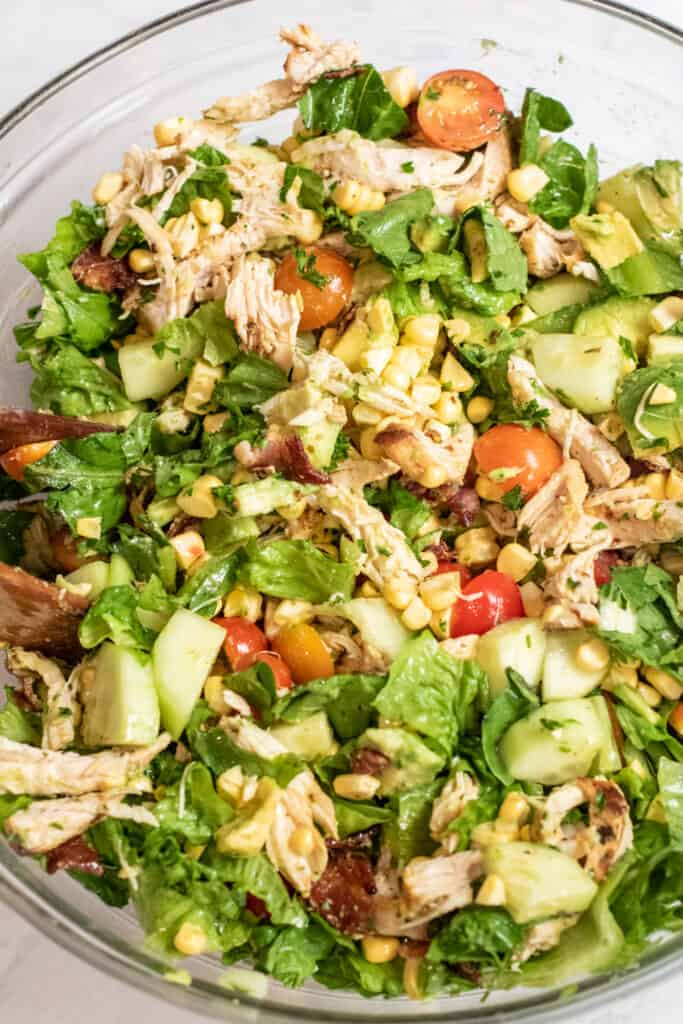 grilled chicken green salad with tomatoes, corn, and avocado in a large bowl