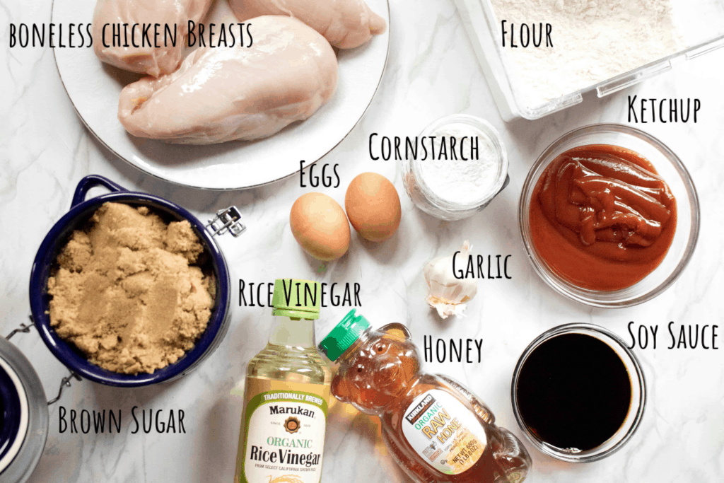 chicken, sugar, ketchup, eggs, honey, rice vinegar, soy sauce, cornstarch, and flour on counter