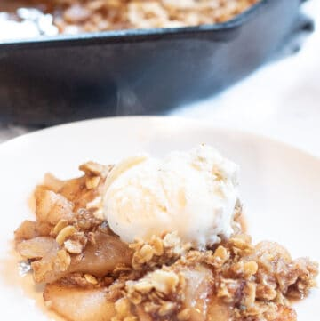 a plate of apple crisp with ice cream on top.