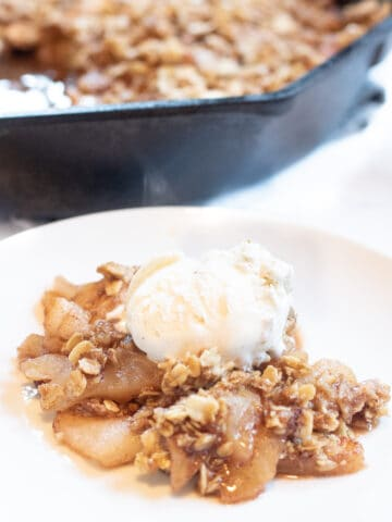 a plate of apple crisp with ice cream on top