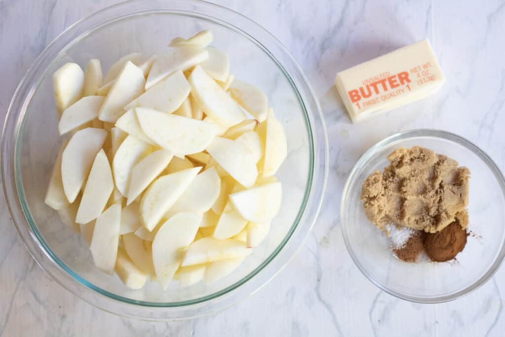 a bowl of sliced apples, butter, and a bowl of brown sugar, cinnamon, salt, and nutmeg.