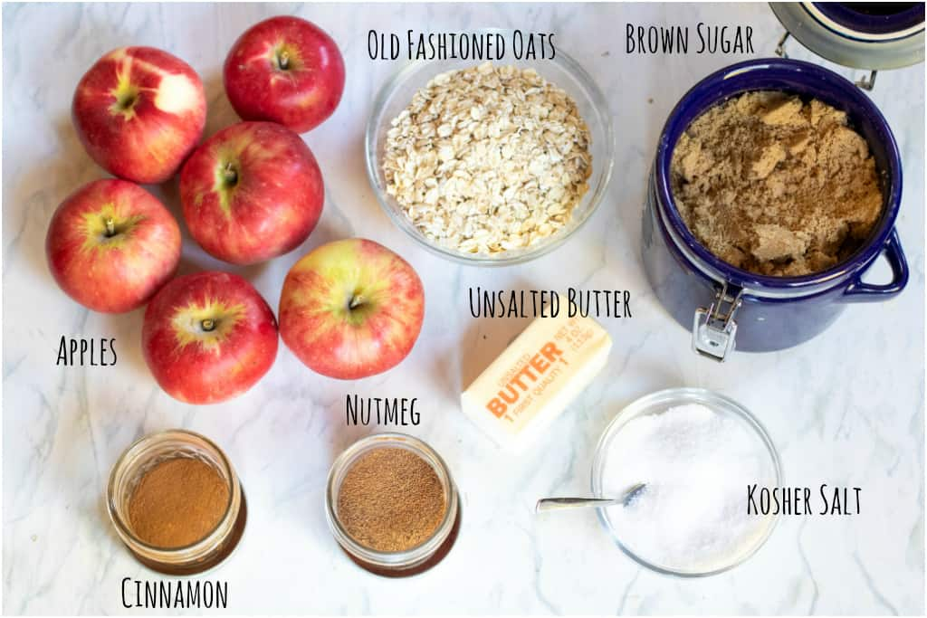 apples, oats, sugar, butter, cinnamon, nutmeg, and salt on a counter.