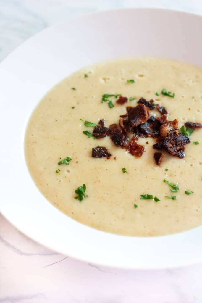 a bowl of soup with crumbled bacon and pasley