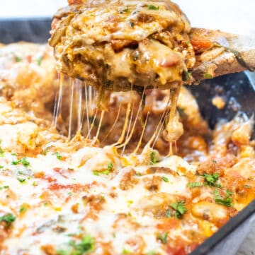 a piece of lasagna coming out of a cast iron skillet.
