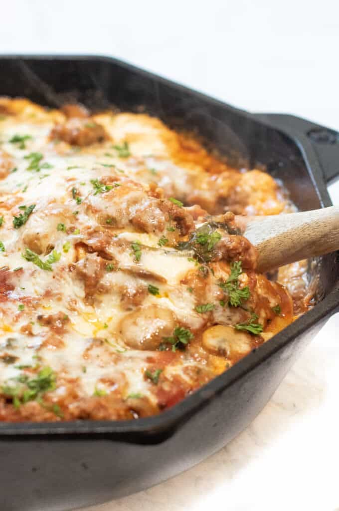 a cast iron lasagna with spoon in it