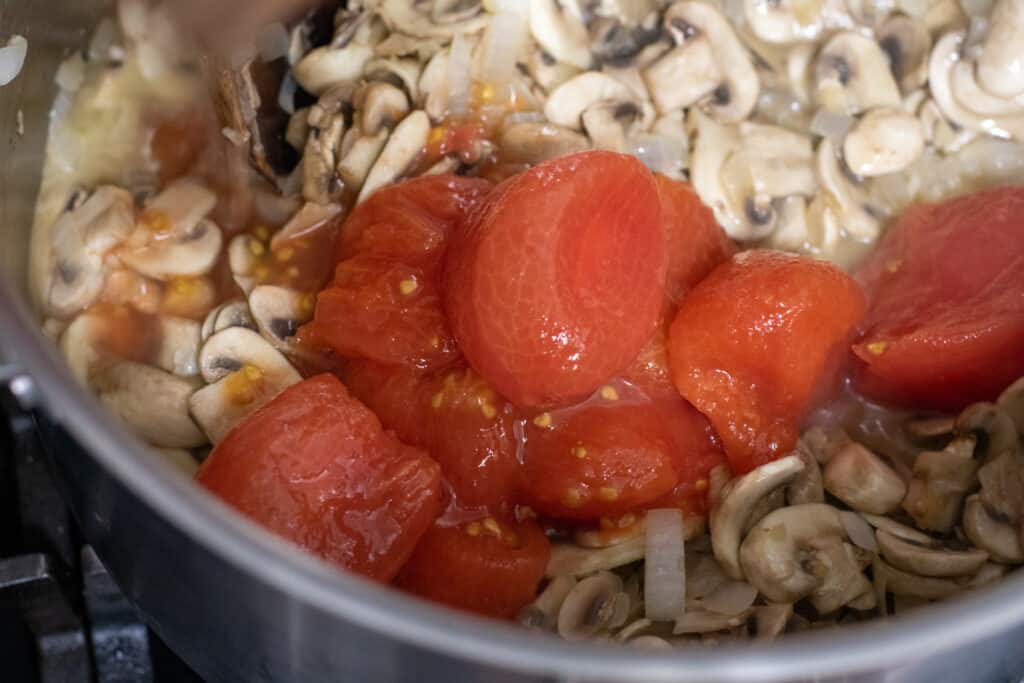 whole tomatoes added to cooked mushrooms in a pan