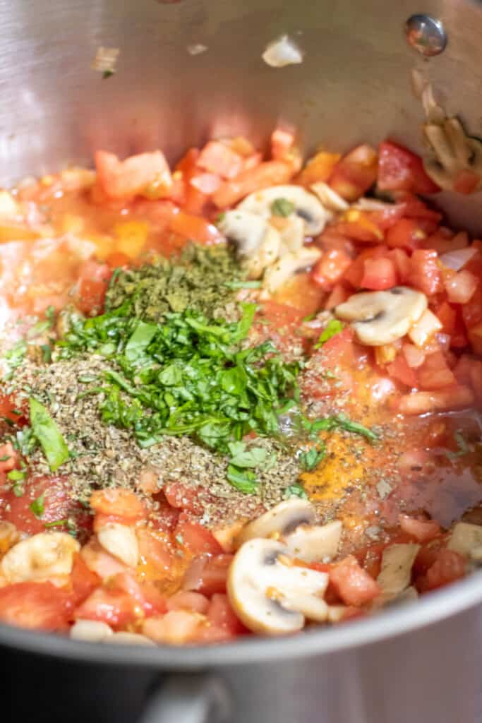 fresh and dried herbs in a pot with fresh diced tomatoes and mushrooms