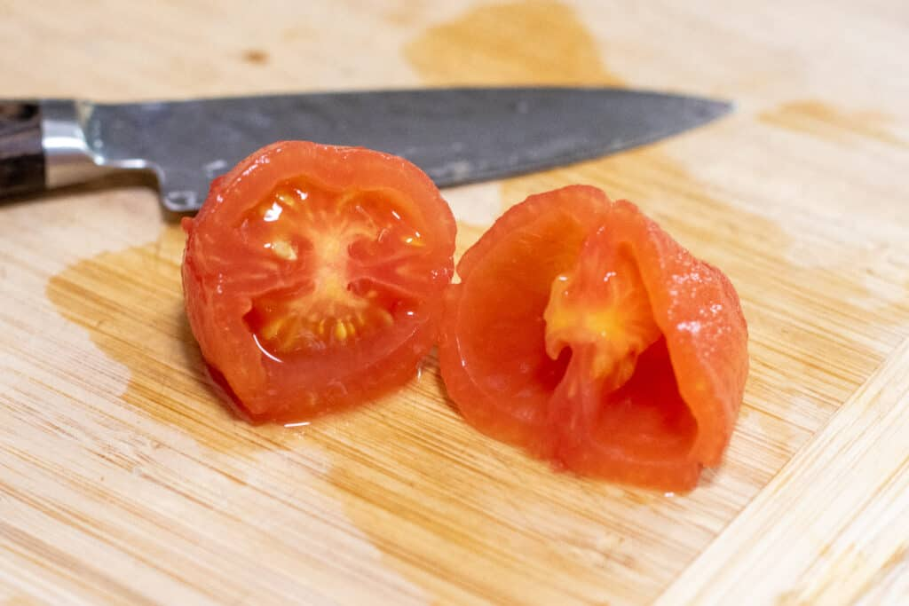 a roma tomato sliced in half on cutting board and one side deseeded