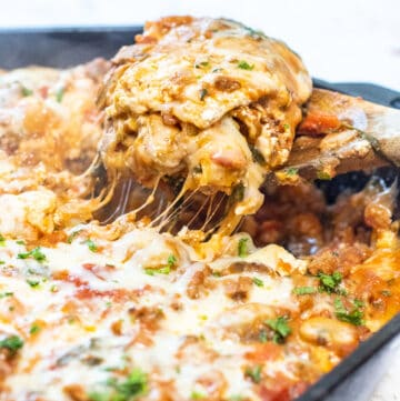 a wooden spoon scooping a big peice of cheesy lasagna from a cast iron.