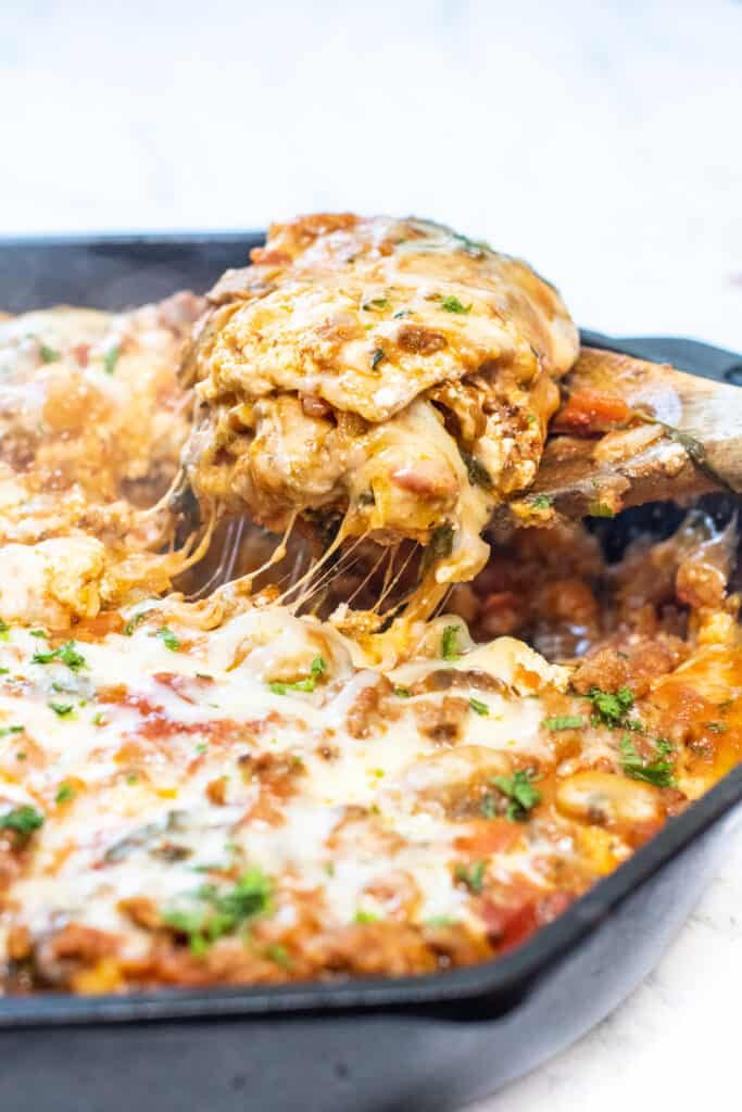 a wooden spoon holding a cheesy piece of lasagna