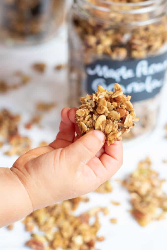 a toddler hand holding a granola cluster