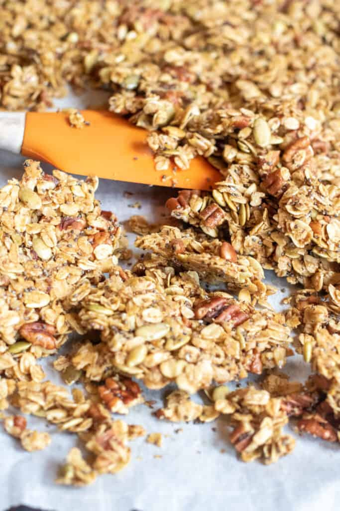 a close up of baked granola with a spatula breaking it into clusters