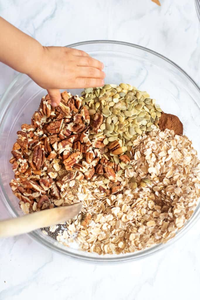 a large bowl with oats, nuts, seeds, and cinnamon with a wooden spoon and a toddler hand